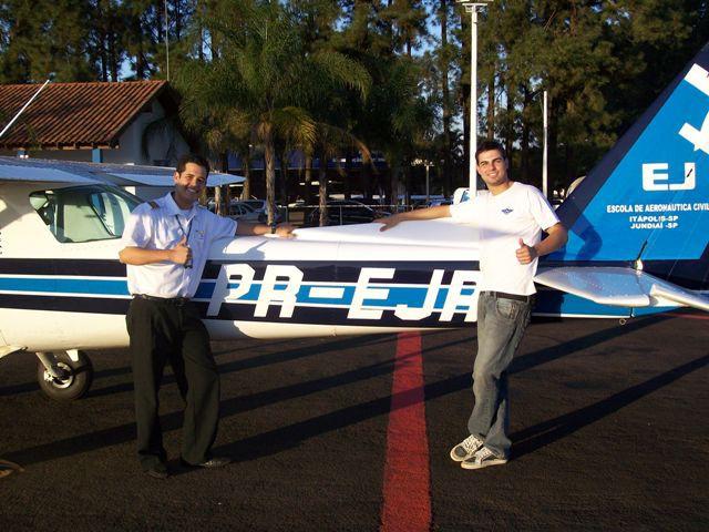 Instrutor Lucas e aluno Bruno posam a frente da aeronave.